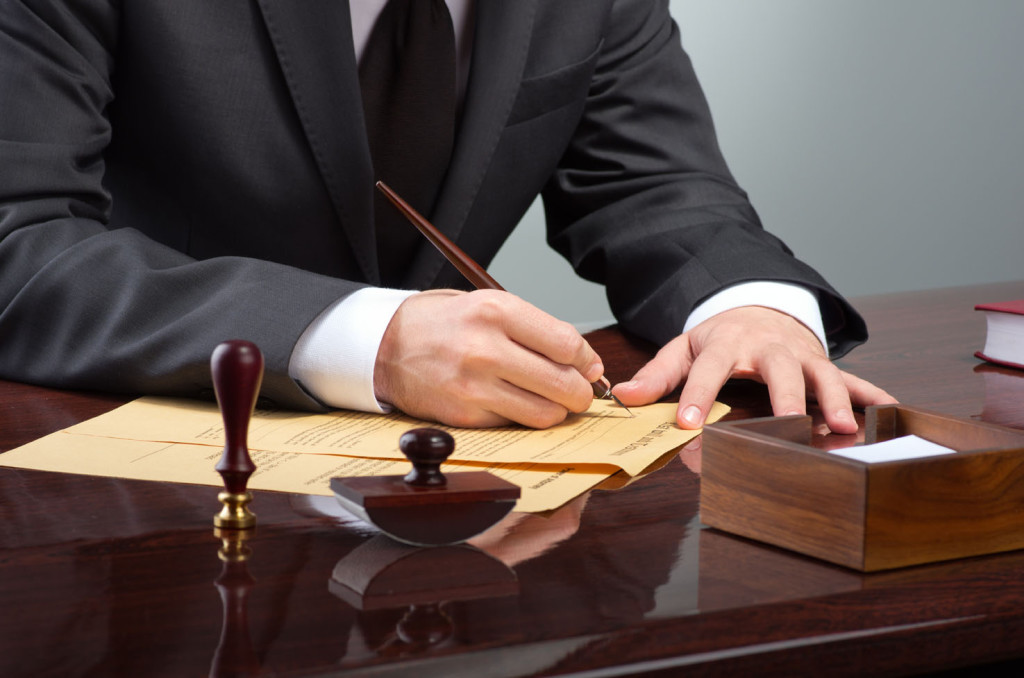 Businessman writing testament at notary public office